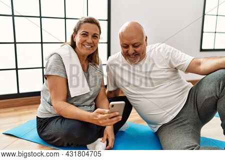 Middle age hispanic couple using smartphone at sport center.