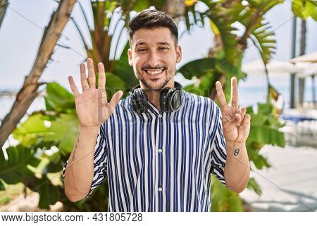 Young handsome man listening to music using headphones outdoors showing and pointing up with fingers number seven while smiling confident and happy.