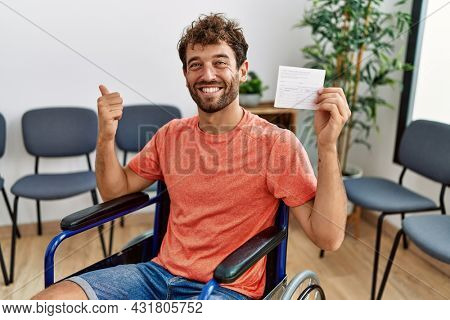 Young handsome man holding covid record card sitting on wheelchair pointing thumb up to the side smiling happy with open mouth