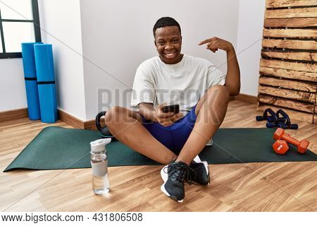 Young african man sitting on training mat at the gym using smartphone looking confident with smile on face, pointing oneself with fingers proud and happy.