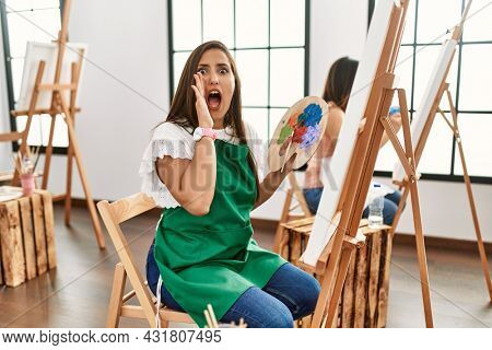 Young hispanic artist women painting on canvas at art studio shouting and screaming loud to side with hand on mouth. communication concept.