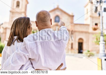 Middle age hispanic couple of husband and wife together on a sunny day outdoors. Pointing to church at the city