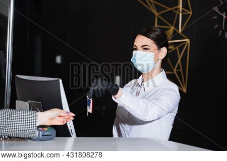 Receptionist In Medical Mask Holding Blurred Room Key Near Guest