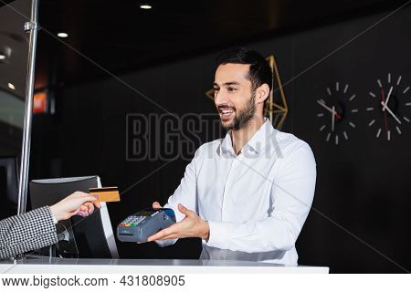 Bearded Receptionist Smiling While Holding Payment Terminal Near Guest With Credit Card