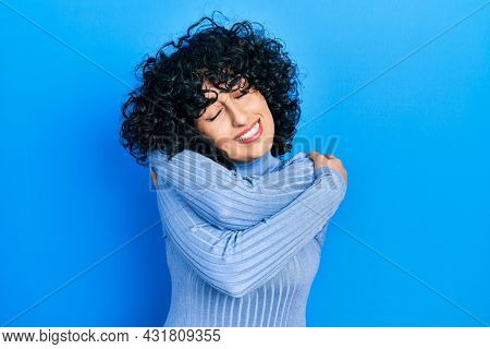 Young middle east woman wearing casual clothes hugging oneself happy and positive, smiling confident. self love and self care