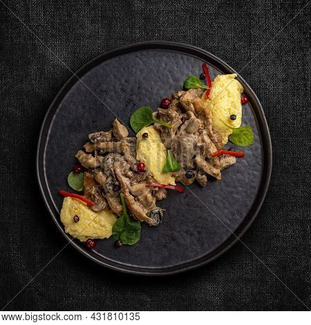 Flat Lay Of Chicken Breast Stewed In Cream Sauce With Mushrooms Served With Polenta