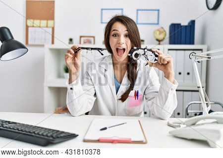 Young doctor woman holding optometry glasses and normal glasses celebrating crazy and amazed for success with open eyes screaming excited.