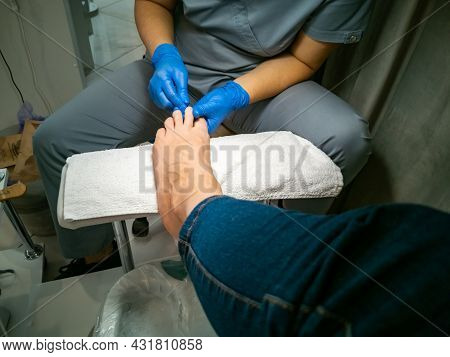 A Gloved Master Makes A Pedicure For A Client. Close-up No Face. Woman In A Nail Salon Paints Her Na