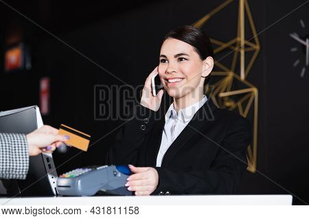 Happy Receptionist Smiling And Talking On Smartphone Near Guest With Credit Card