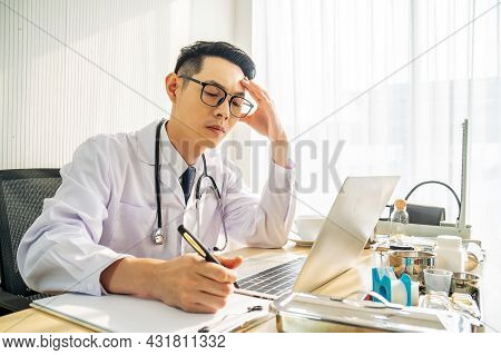 Troubled Asian Man Doctor Working On Computer At Desk In Hospital Clinic, Worried, Thinking Hard, He