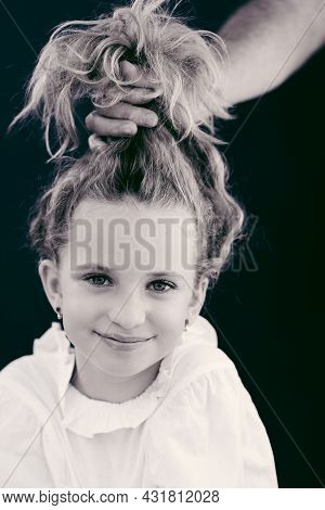 Emotional Portrait Of Young Beautiful Girl. The Father's Hand Holds Her Hair In A Bun Above The Girl