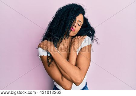 Middle age african american woman wearing casual white t shirt hugging oneself happy and positive, smiling confident. self love and self care