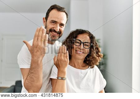 Middle age hispanic couple smiling happy on marriage proposal. Standing at home showing engagement ring on finger.