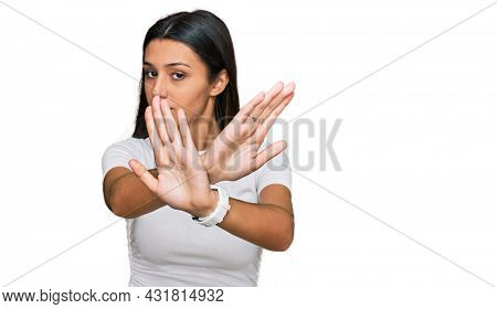 Young hispanic girl wearing casual white t shirt rejection expression crossing arms doing negative sign, angry face