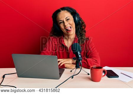 Beautiful middle age woman working at radio studio sticking tongue out happy with funny expression. emotion concept.