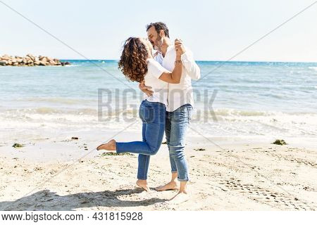 Middle age hispanic couple kissing and hugging at the beach.