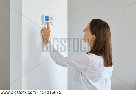 Indoor Shot Of Young Adult Woman Regulating Heating Temperature With A Modern Wireless Thermostat In