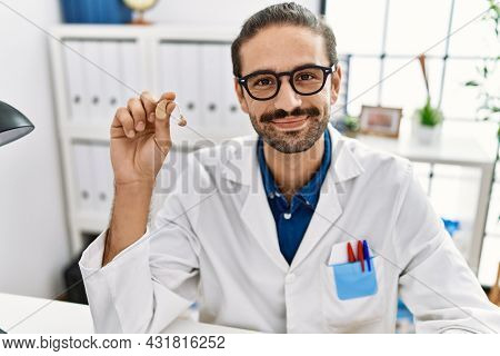 Young hispanic doctor man holding medical hearing aid looking positive and happy standing and smiling with a confident smile showing teeth