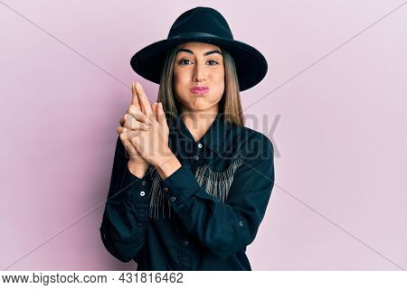 Young hispanic woman wearing cowgirl style doing pistol gesture with hands puffing cheeks with funny face. mouth inflated with air, catching air.