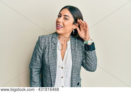 Young hispanic woman wearing business clothes smiling with hand over ear listening an hearing to rumor or gossip. deafness concept.