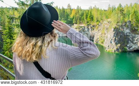 Young Woman Wearing Black Hat And Warm Sweater Is Standing By The Scenic View Of The Lake In Marble
