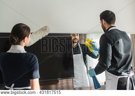 Housekeepers Doing Cleaning In Hotel Room With Cleaning Supplies
