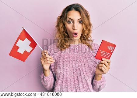 Young caucasian woman holding swiss flag and passport afraid and shocked with surprise and amazed expression, fear and excited face.