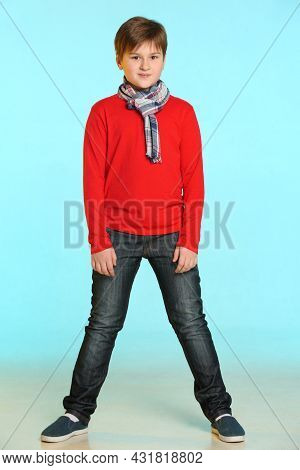 Fashionable And Handsome Teenage Boy Wearing A Red Sweater And Plaid Scarf. He Poses In Full Height