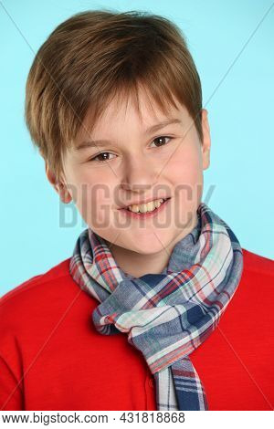 Close-up Portrait: Fashionable, Cheerful Teenage Boy In A Red Sweater And A Checkered Scarf. He Smil