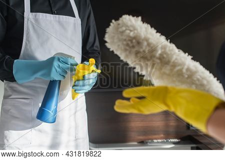 Cropped View Of Housekeepers With Cleaning Supplies