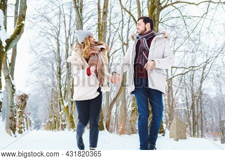 Young Happy Couple Smile To Each Other And Walk In Winter Park Holding Hands. Man And Woman Have Fun