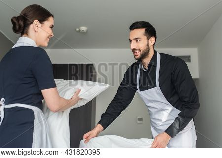 Positive Housekeepers Changing Bedding In Modern Hotel Room