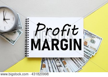 Profit Margin, Gray And Yellow Background. The Inscription On The Notebook Near The Money