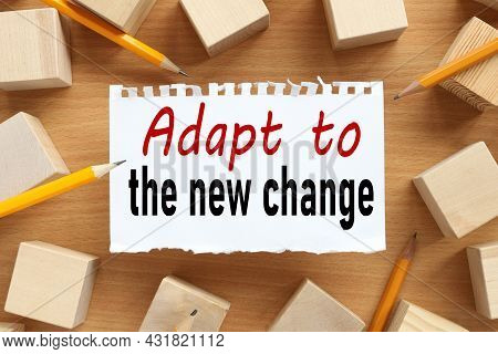 Adapt To The New Changes, Text On White Torn Paper. Near The Wooden Cubes