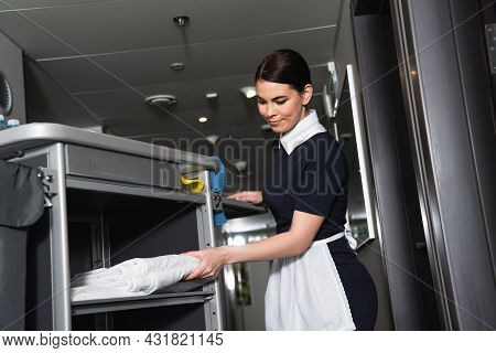 Brunette Maid In Uniform Taking Clean Bed Sheets From Housekeeping Cart