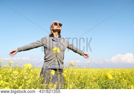 Asian Woman Tourist Embracing Nature In A Field Of Canola Flowers