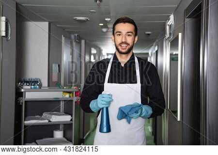 Joyful And Bearded Housekeeper In Rubber Gloves Looking At Camera In Corridor Of Hotel