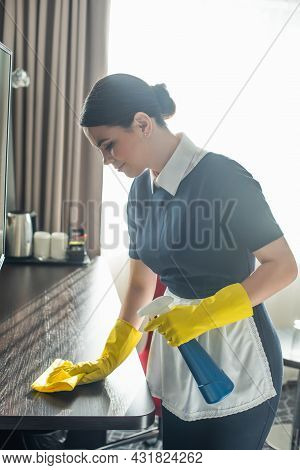 Side View Of Maid In Rubber Gloves Cleaning Wooden Surface With Rag