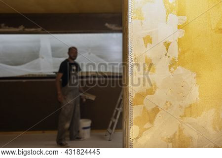 Abstract Creative Background With Stains Of Yellow Paint-primer On Rough White Wall. Industrial Back