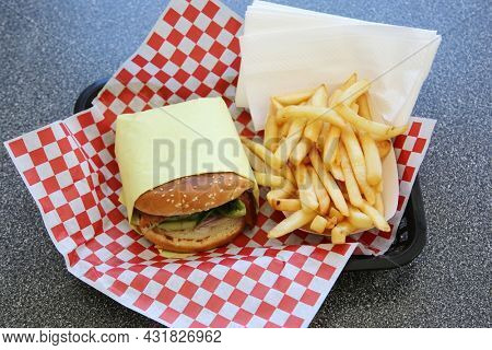 Cheeseburger with french fries. Lunch of Fresh Grilled Cheese Burger and French Fries on a red and white checker place mat in a fast food restaurant. Everyone enjoys Cheese Burgers and Fries for Lunch