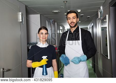 Cheerful Housekeepers In Rubber Gloves Looking At Camera In Corridor Of Hotel