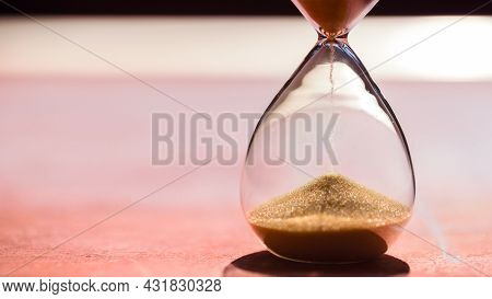 Gold Sand Running Through The Bulbs Of An Hourglass Measuring The Passing Time In A Countdown To A D
