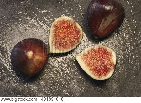 Still Life With Organically Grown Figs; One Of Them Split In Half, On A Dark Slate Background.