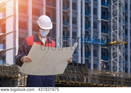Low Angle View Of Engineer Builder In Protective Face Mask Looking At Project Blueprint While Workin