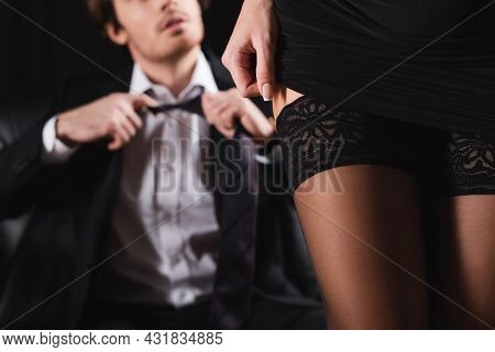 Partial View Of Seductive Woman In Sexy Stockings Near Blurred Man In Suit On Black