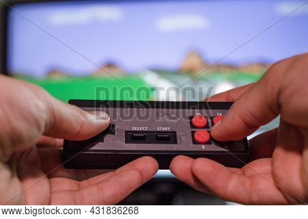 A Man's Hands Hold A Joystick In The Background Of A Tv Screen With A Video Game. Home Entertainment