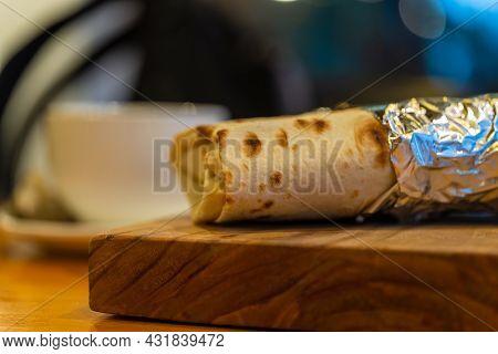 Shawarma, Kebab In Foil Lies On A Wooden Base