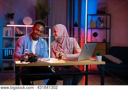 Two Multi Ethnic Coworkers Smiling And Talking While Sitting At Workplace During Evening Time. Arabi