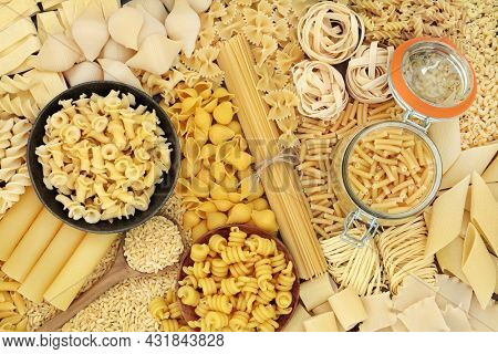 Large collection of dried Italian pasta food varieties forming an abstract background. Flat lay top view.