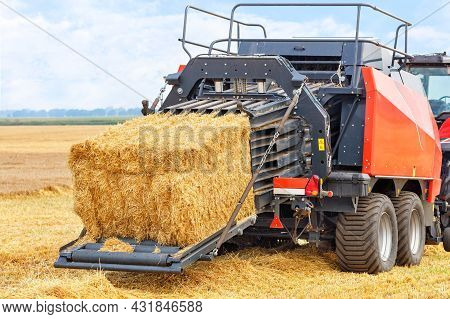 During Harvesting, A Tractor In A Wheat Field Forms Sheaves Of Straw Into Dense Briquettes Using A T